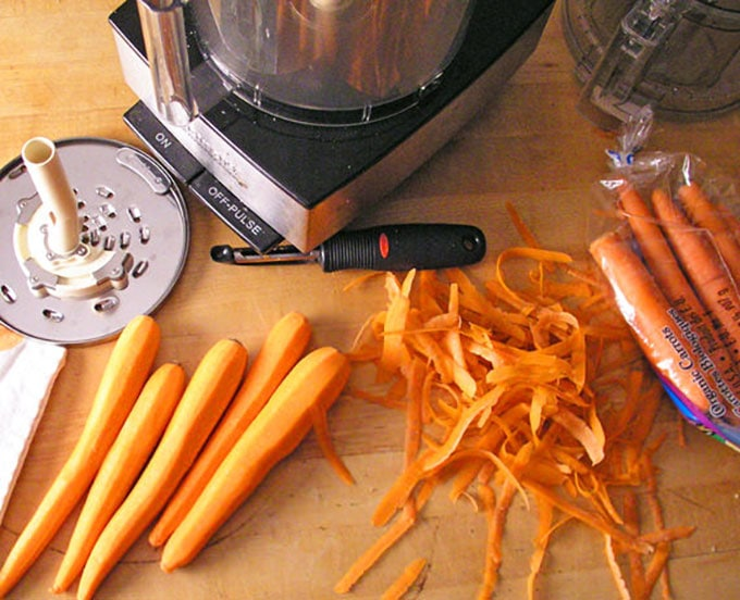 peeled carrots and carrot peelings on a counter next to a food processor and the shredding blade
