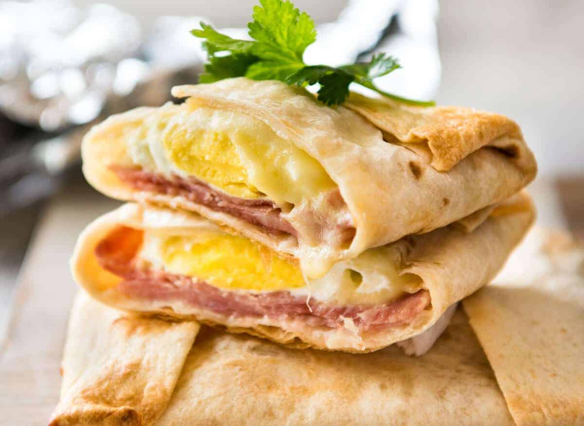 Stack of hot Ham, Egg and Cheese Pockets made with tortillas cut to show the inside with molten cheese and perfectly cooked egg.